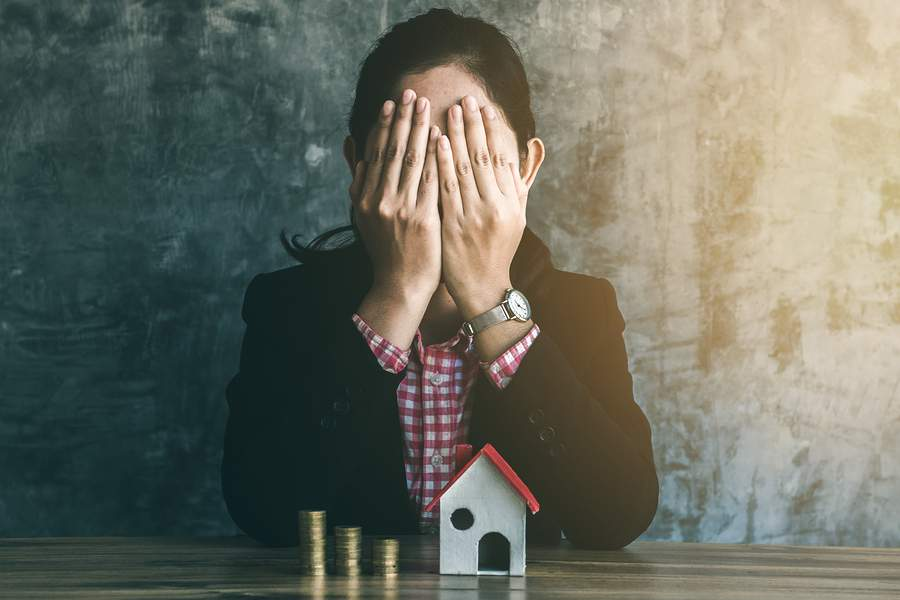 Woman with miniature house and stack of coins experiencing buyer's remorse
