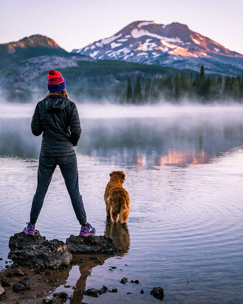 Woman with her dog at Sparks Lake, a destination for Eugene and Bend homeowners