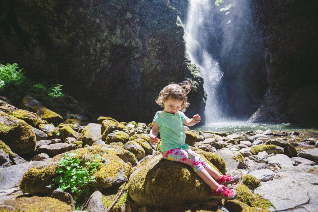 Little girl sitting on mossy rock in front of waterfall in Oregon