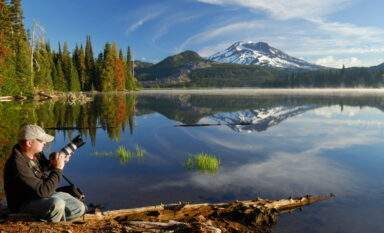 Photographer on shore of calm Sparks Lake with South Sister mountain