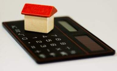 Toy house on top of calculator depicting number crunching for home purchase