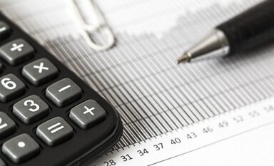 Calculator, graph and pen depicting real estate market analysis