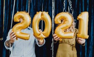 Couple holding balloons header for 2021 real estate forecast