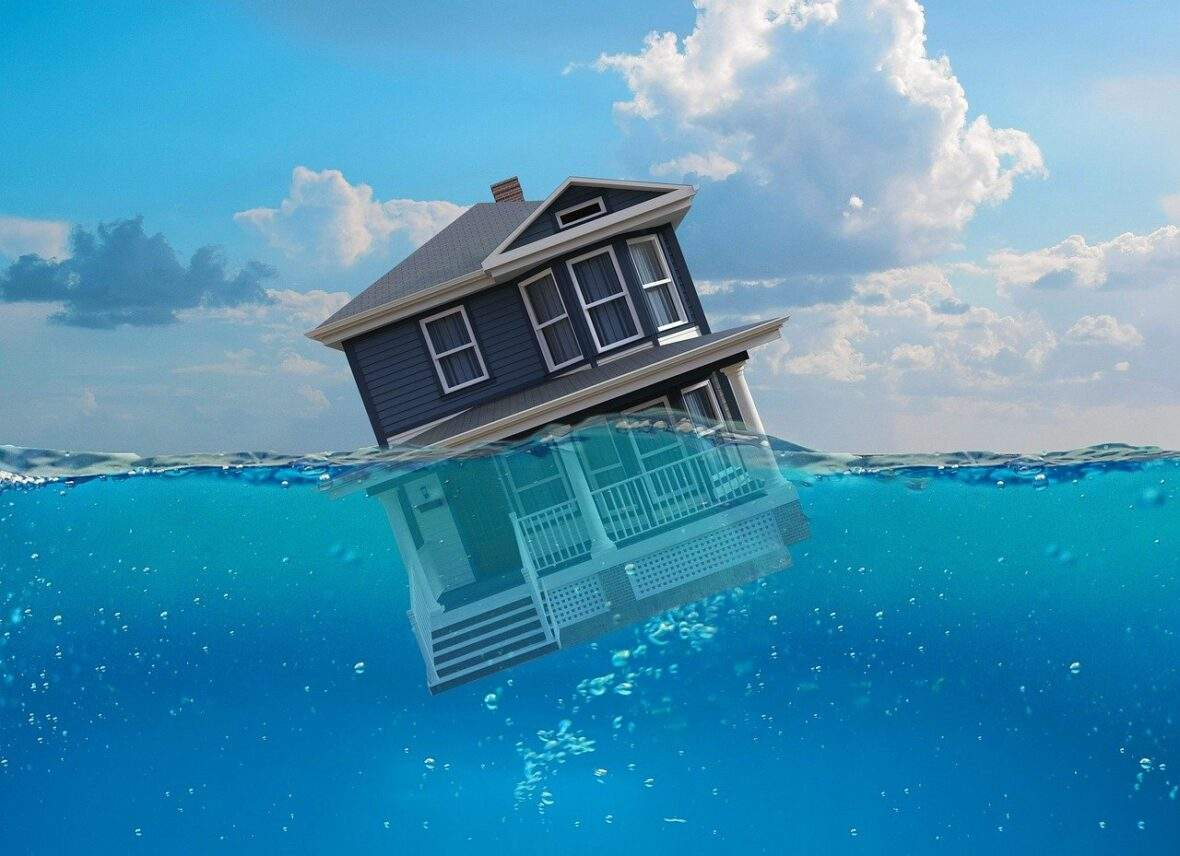 home sinking in water depiction of real estate bubble